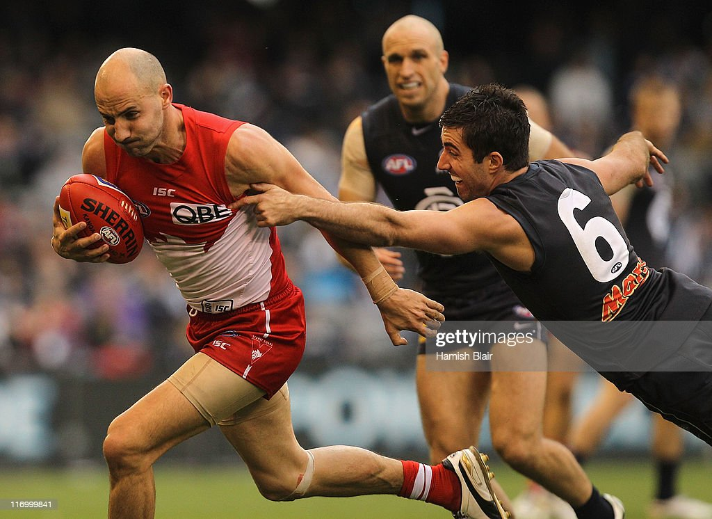 Tadhg Kennelly of the Swans is tackled by Kade Simpson of the Blues during the round 13 AFL match between the Carlton Blues and the Sydney Swans at Etihad Stadium on June 19, 2011 in Melbourne, Australia.