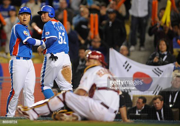 Tae Kyun Kim of Korea is congratulated by Kyung Oan Park after sliding safe at home over catcher Ramon Hernandez of Venezuela in the sixth of the...