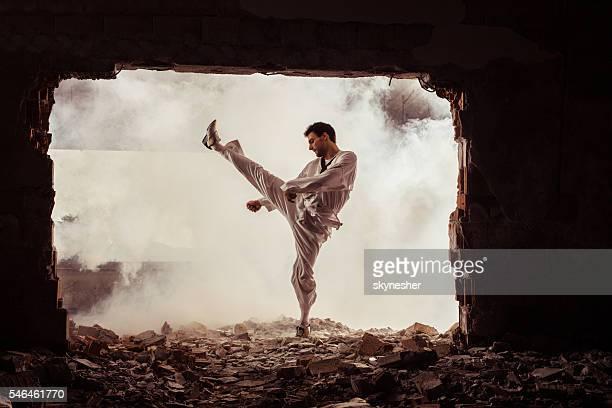 Taekwondo fighter practicing martial arts among ruins.