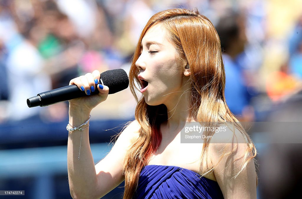 Taeyeon of Korean Pop group Girls Generation sings the Korean national anthen during Korea Day ceremonies before the game between the Cincinnati Reds and the Los Angeles Dodgers at Dodger Stadium on July 28, 2013 in Los Angeles, California.