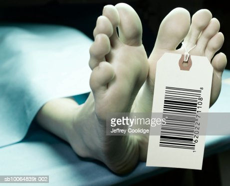 Tag with identification bar code on toe of female corpse in morgue