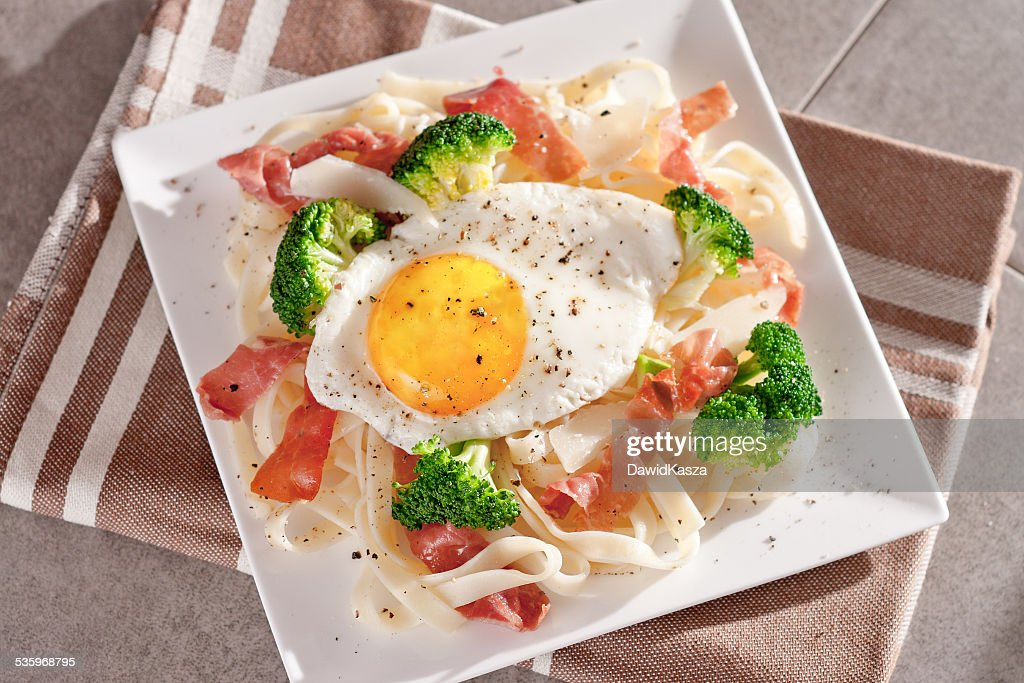 Tagliatelle pasta with broccoli, prosciutto and fried egg. : Stock Photo