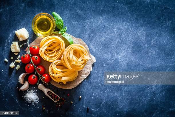 Tagliatelle with ingredients on dark table