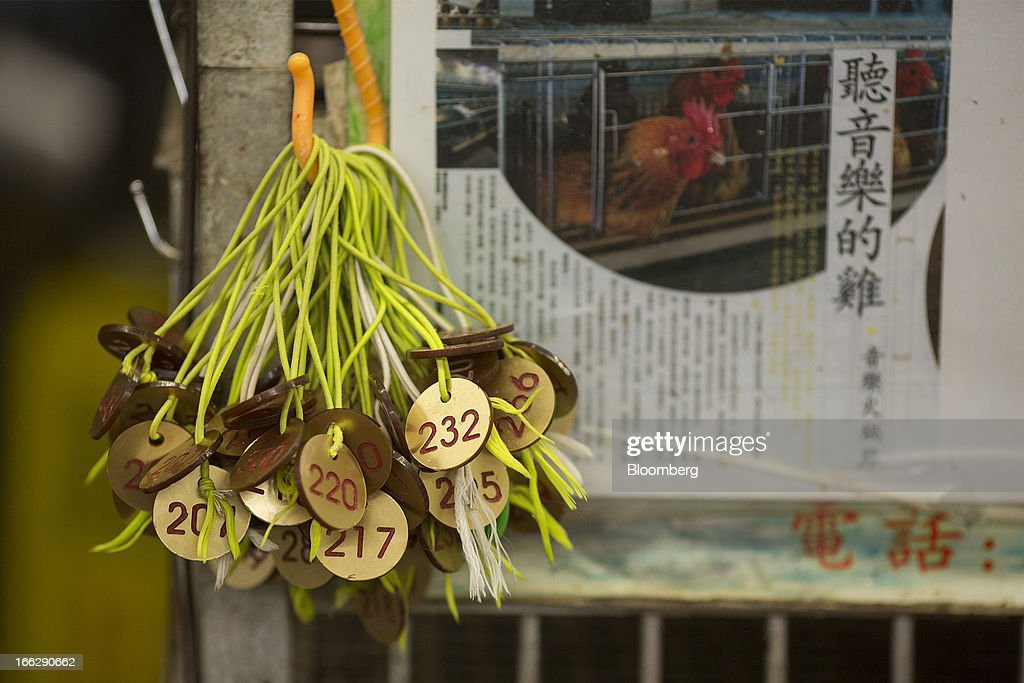 Tags for chickens hang on a hook outside a live poultry stall at the Kowloon City Market in Hong Kong, China, on Thursday, April 11, 2013. The Hang Seng Index rose 0.8 percent to 22,220.65 as of 1:14 p.m. in Hong Kong, headed for its longest winning streak since March 27. The gauge is close to erasing last week's loss prompted by the outbreak of a new strain of bird flu in China. Photographer: Jerome Favre/Bloomberg via Getty Images
