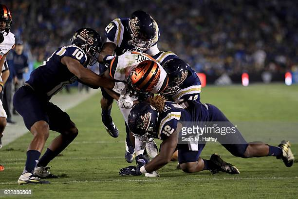 Tahaan Goodman Fabian Moreau Jayon Brown and Kenny Young of the UCLA Bruins tackle Artavis Pierce of the Oregon State Beavers during the first half...