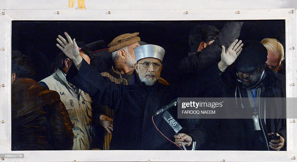 Tahir-ul Qadri, a Pakistani religious leader, gestures in front of a bullet proof glass upon his arrival at a protest march in Islamabad on early January 15, 2013. Tens of thousands of Pakistani protesters streamed towards Islamabad on Monday, led by a cleric calling for revolution but accused of trying to sow political chaos ahead of elections. AFP PHOTO/Farooq NAEEM