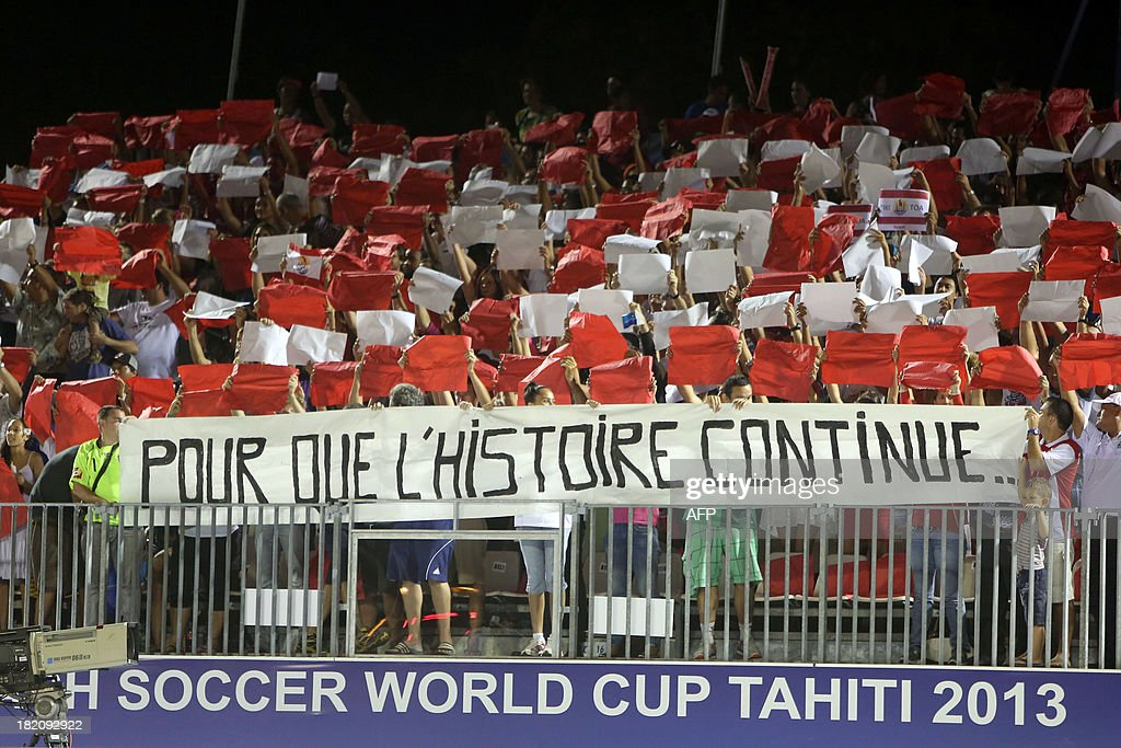 Tahiti's supporters hold a banner reading 'So that the story continues...' during the 2013 FIFA beach soccer World Cup semifinal match between Russia and Tahiti on September 27, 2013 on the French Polynesian island of Tahiti. Russia won 5-3.