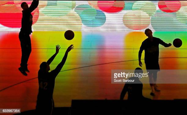 Tai Wesley of Melbourne United and his teammates are silhouetted by an electronic advertising board as they warm up during the round 18 NBL match...