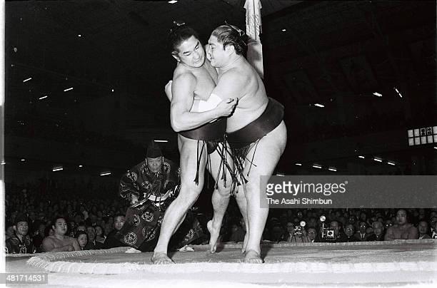 Taiho throws Takanohana during day five of the Grand Sumo New Year Tournament at Kuramae Kokugikan on January 14 1971 in Tokyo Japan