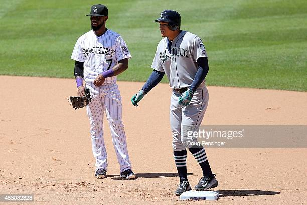 Taijuan Walker of the Seattle Mariners arrives at second base with an RBI double as shortstop Jose Reyes of the Colorado Rockies looks on giving the...