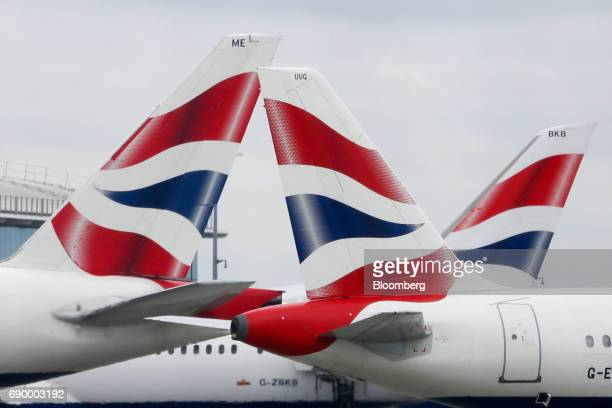 Tail fins sit on passenger aircraft operated by British Airways a unit of International Consolidated Airlines Group SA on the tarmac at London...