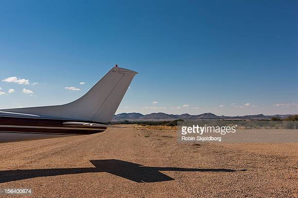 Tail of small plane on dirt runway
