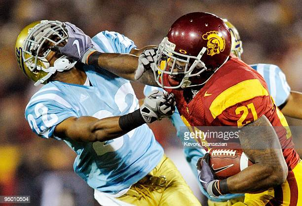Tailback Allen Bradford of the USC Trojans stiff arms defensive back Sheldon Price of the UCLA Bruins as he runs for a gain during the second quarter...