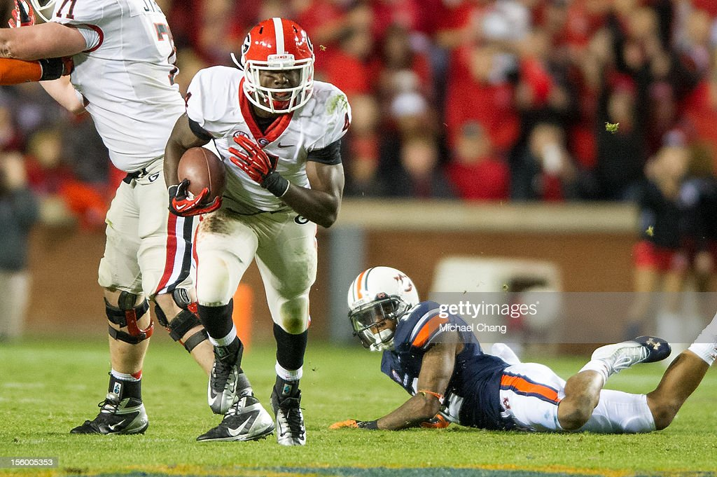Tailback Keith Marshall #4 of the Georgia Bulldogs escapes a tackle by defensive back Demetruce McNeal #12 of the Auburn Tigers on November 10, 2012 at Jordan-Hare Stadium in Auburn, Alabama. Georgia defeated Auburn 38-0 and clinched the SEC East division.