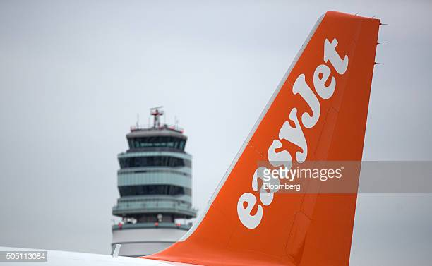A tailfin of an EasyJet Plc passenger aircraft stands in front of the control tower at Vienna International Airport operated by Flughafen Wien AG in...