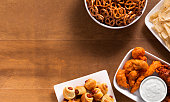 a aerial view of tailgating/party spread of hot wings, chicken fingers, pretzels and nachos with blank space for text.  Please see my portfolio for other food and drink images.