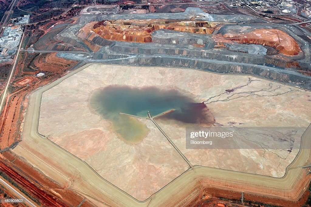 A tailings dam sits in front of a waste dump at the Fimiston Open Pit mine known as the Super Pit in this aerial photograph taken above Kalgoorlie...