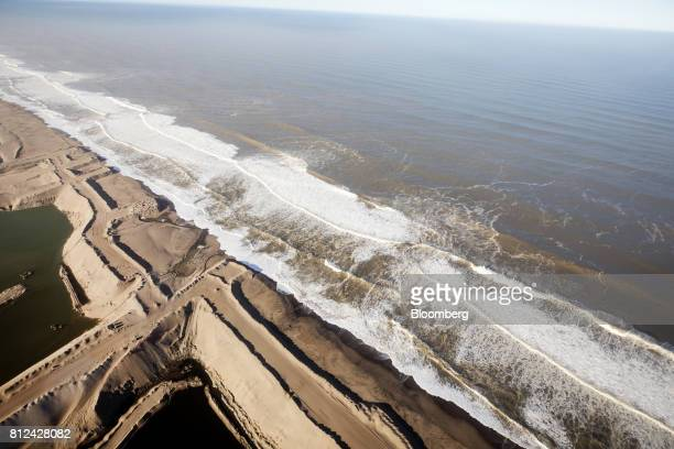 Tailings from open pit diamond mines once operated by De Beers sit along the shoreline of the Atlantic Ocean on the Skeleton Coast off the coast of...
