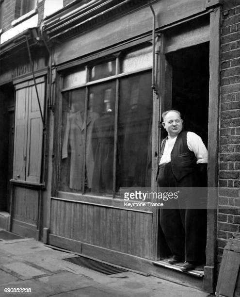 Tailleur photographié sur le pas de porte de son magasin sur Cable Street à Londres RoyaumeUni