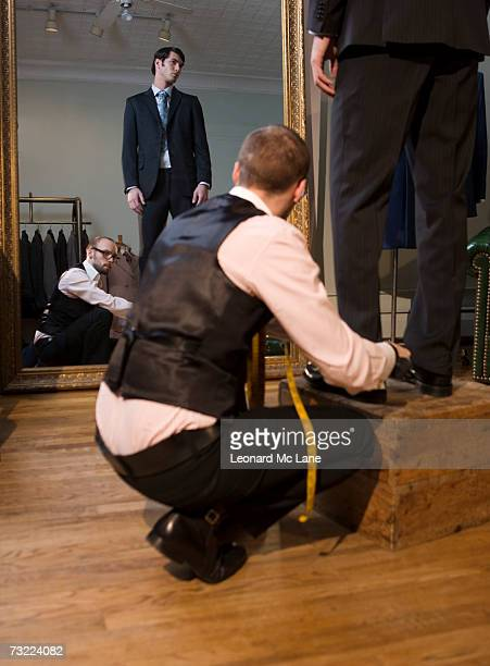 Tailor adjusting man's trousers, close-up