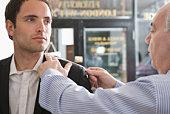 Tailor adjusting suit jacket for customer