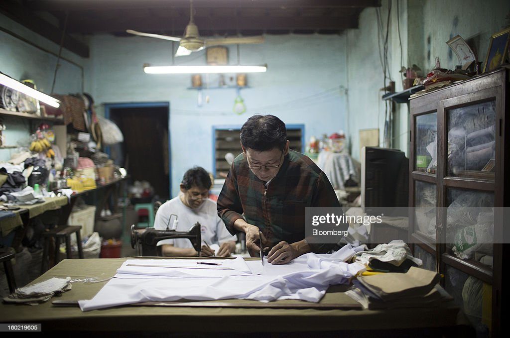 A tailor cuts cloth inside a workshop in Pathein, Myanmar, on Thursday, Jan. 17, 2013. Myanmar cleared about $1 billion in overdue debt with the Asian Development Bank and World Bank using a bridge loan from Japan, opening the door for increased lending as the country seeks to overhaul its infrastructure. Photographer: Brent Lewin/Bloomberg via Getty Images