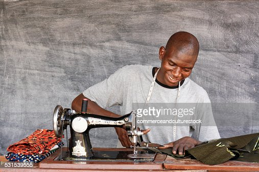 A tailor cutting a cloth with scissors