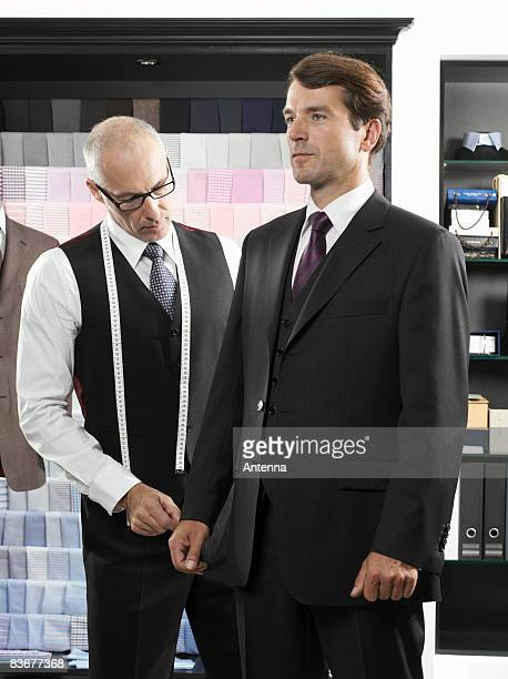 A tailor fitting a man with a suit