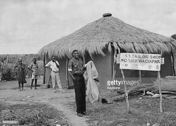 A tailor holding some of his work outside his shop in Serowe Bechuanaland Protectorate March 1950