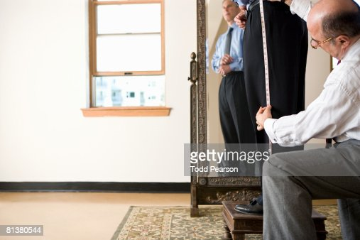 Tailor measures pant length : Stock Photo