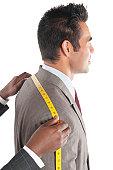 Tailor measuring across upper back from shoulder to shoulder of customer