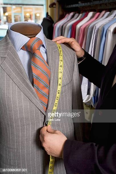 Tailor measuring jacket on dressmaker's model