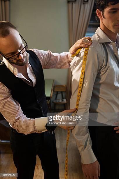 Tailor measuring man in shirt, close-up