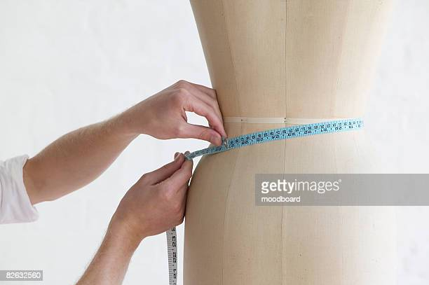 Tailor measuring mannequin, close up of hands