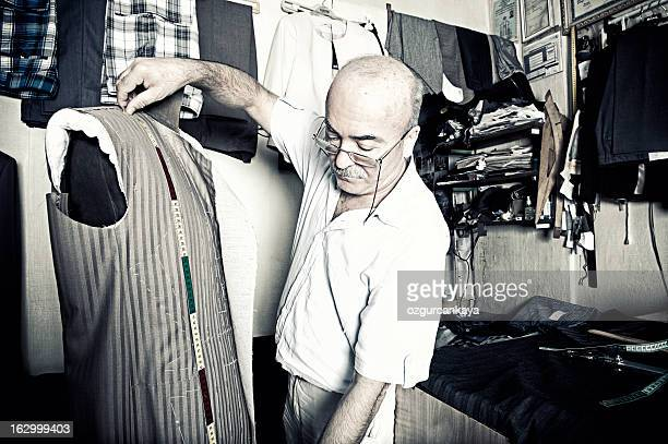 Tailor measuring the length of a waist coat