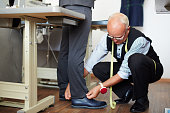 Confident mature tailor with measuring tape on his neck and needle case on wrest sitting on haunches and measuring necessary length of trousers for client