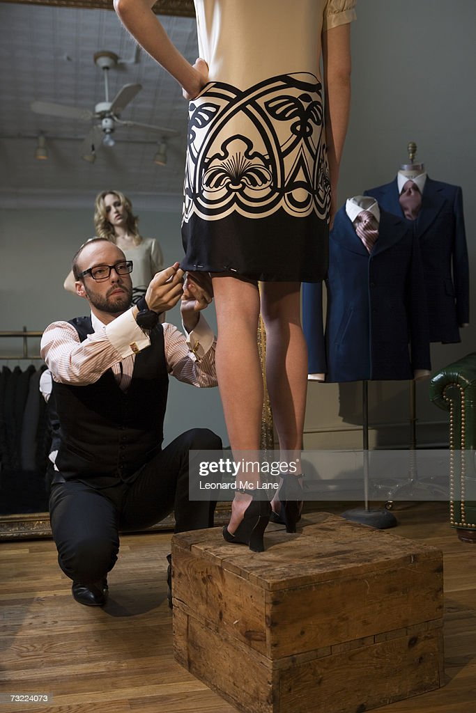 Tailor pinning female model's skirt, model with hand on hip : Stock Photo