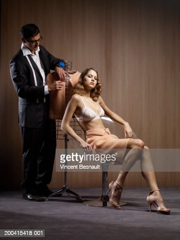 Tailor pinning jacket on dressmaker's model by woman in bra in chair : Stock Photo