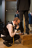 Tailor pinning male model's trousers