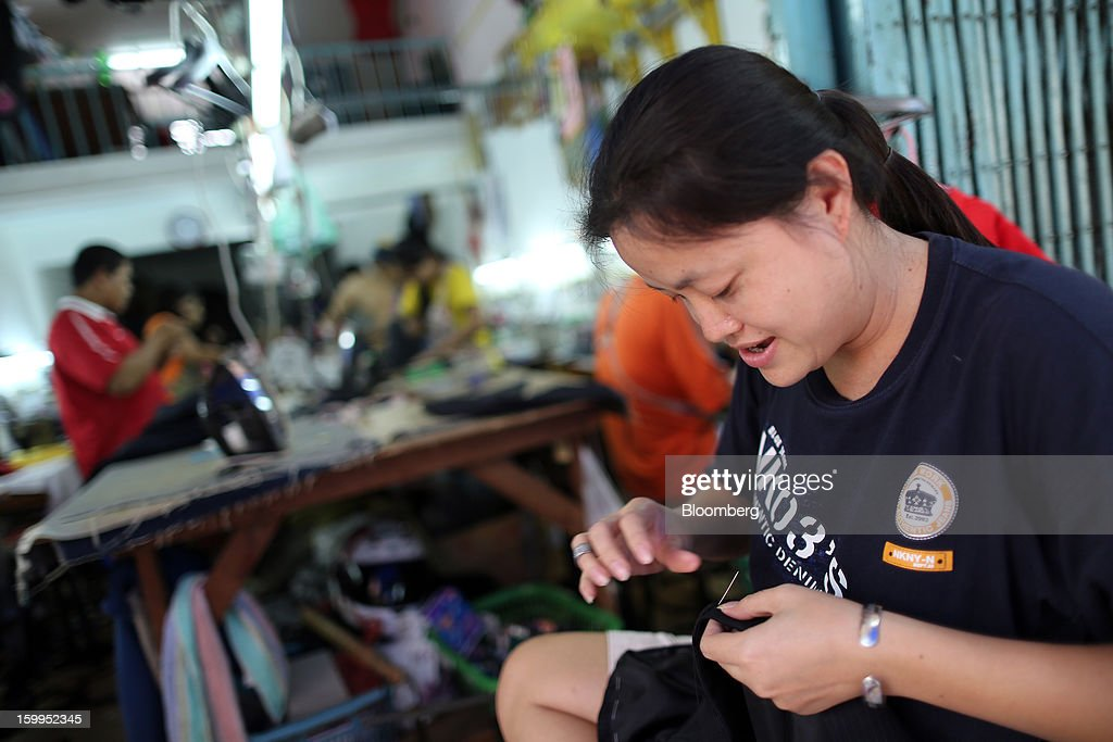 A tailor sews clothing at a workshop in Bangkok, Thailand, on Wednesday, Jan. 23, 2013. Prime Minister Yingluck Shinawatra's government last month approved a new round of increases in the daily minimum wage to 300 baht ($9.8) from the beginning of this year, after a similar raise in April in seven provinces including Bangkok. Photographer: Dario Pignatelli/Bloomberg via Getty Images
