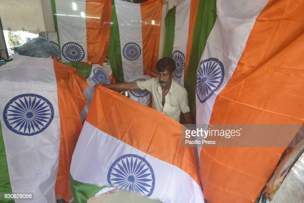 A tailor stitches Indian National tricolor flag ahead of the Dependence Day at Agartala