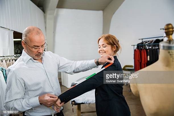Tailor taking measures of customer.