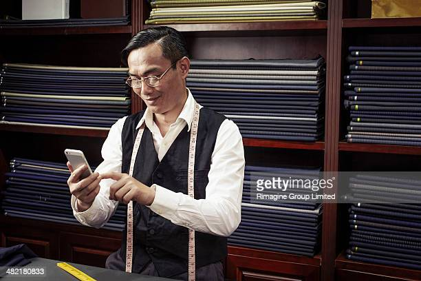 Tailor texting on cellphone in tailors shop