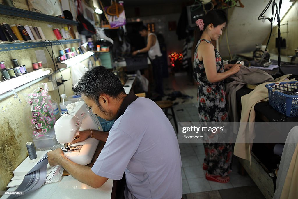Tailors make clothes at a workshop in Bangkok, Thailand, on Wednesday, Jan. 23, 2013. Prime Minister Yingluck Shinawatra's government last month approved a new round of increases in the daily minimum wage to 300 baht ($9.8) from the beginning of this year, after a similar raise in April in seven provinces including Bangkok. Photographer: Dario Pignatelli/Bloomberg via Getty Images