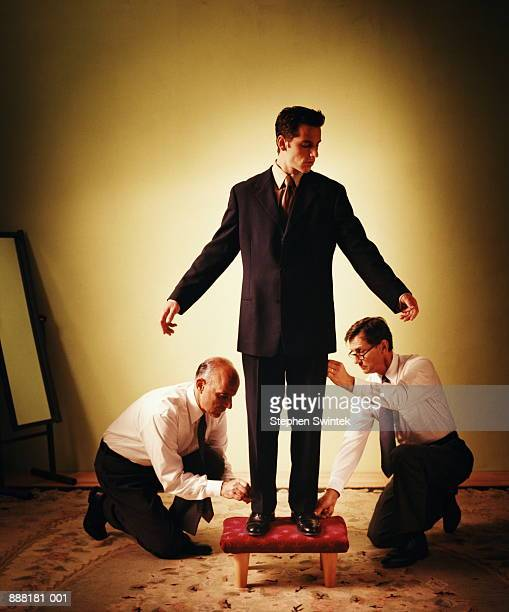 Tailors measuring and adjusting man's trousers