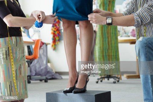 Tailors pinning a dress