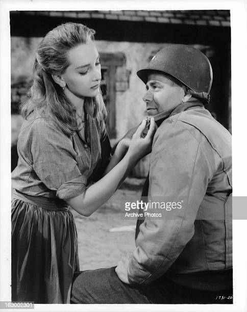 Taina Elg fastens a star on Glenn Ford's colar in a scene from the film 'Imitation General' 1958