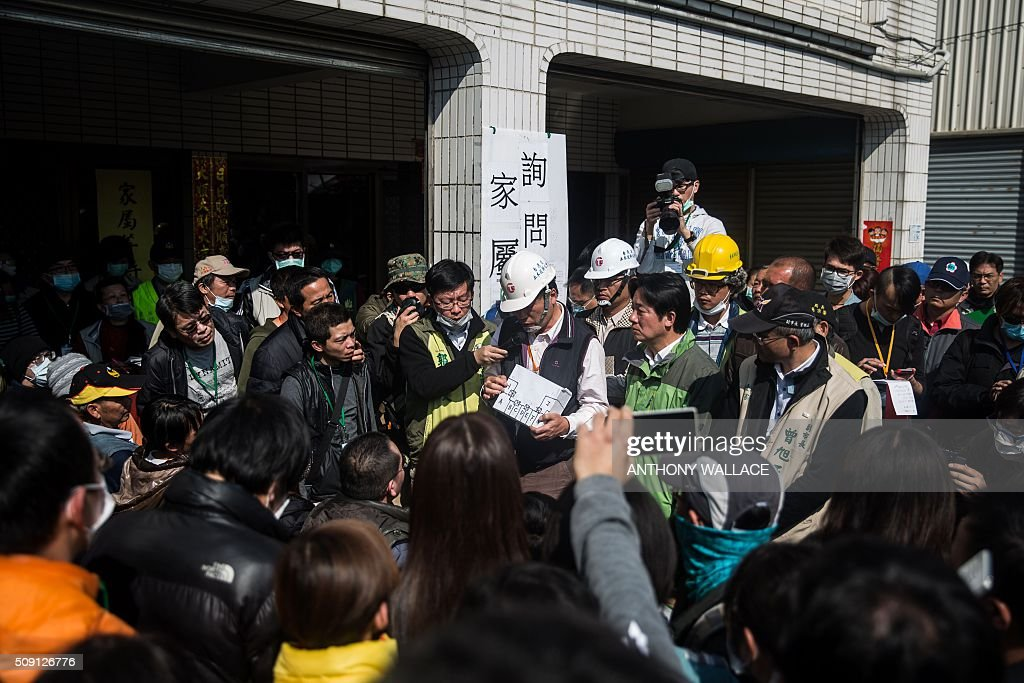 Tainan's Mayor William Lai (centre R, in green) and Cheng Ming-chang (C) president of Tainan civil engineers association brief relatives on the rescue operation of a building which collapsed in the 6.4 magnitude earthquake, in the southern Taiwanese city of Tainan on February 9, 2016. Rescuers deployed heavy machinery on February 9 in a renewed effort to locate more than 100 people trapped in the rubble of a Taiwan apartment complex felled by an earthquake as the 72-hour 'golden window' for finding survivors passed. AFP PHOTO / ANTHONY WALLACE / AFP / ANTHONY WALLACE