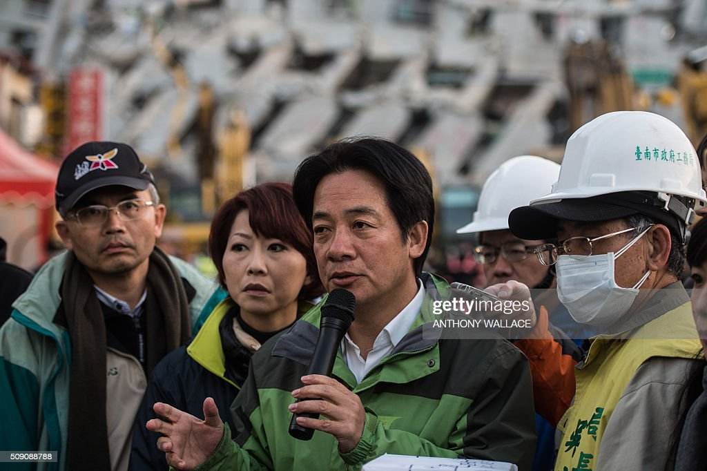 Tainan's mayor William Lai (C) briefs the press on the current status of the search and rescue operation in a building (background) which collapsed in the 6.4 magnitude earthquake, in the southern Taiwanese city of Tainan early on February 9, 2016. Rescuers are set to start using diggers and extractors to remove giant concrete slabs once they have ensured all residents from the upper parts of the rubble have been freed. AFP PHOTO / ANTHONY WALLACE / AFP / ANTHONY WALLACE