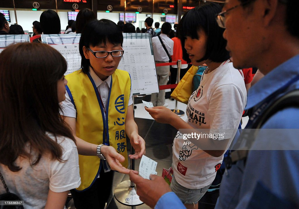 A Taipei Main Station employee answers questions for visitors at Taipei's main station as Typhoon Soulik approaches northern Taiwan on July 12, 2013. Hundreds of villagers were evacuated and schools and businesses shut down in Taiwan on July 12 as it prepared for the arrival of Typhoon Soulik, expected to pound the island with powerful winds and heavy rain over the weekend. AFP PHOTO / Mandy CHENG